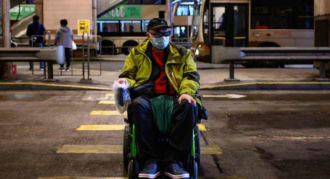 Persona con discapacidad trasladándose con protección frente al covid-19 con su silla de ruedas.